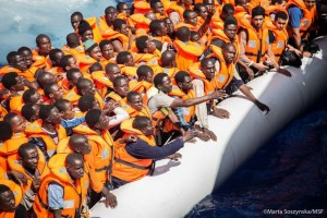 Rubber boat filled with migrants wearing lifejackets.
