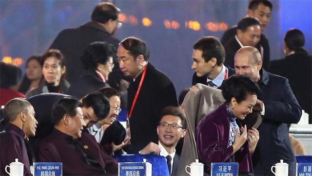 """La prensa oficial rusa dice que fue un gesto de la caballerosidad de su presidente Vladimir Putin, con la primera dama china Peng Liyuan, mientras que la prensa oficial china… ¡no se oye Padre!  El caso del """"Abrigogate"""" estalló en las redes sociales chinas desde que la televisión estatal difundió las imágenes y la comentarista hasta describió la escena: """"Putin le coloca el abrigo a Peng Liyuan"""". Pocos segundos después, ya era un #hashtag."""