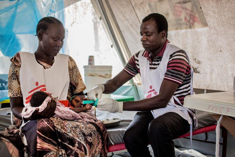 """Un año después de que estallaran los combates en la región del Alto Nilo, en Sudán del Sur, muchos de los que huyeron de la violencia permanecen todavía en la aldea de Aburoc, donde buscaron refugio. En breve tendrán que hacer frente a una difícil elección: quedarse en la zona, donde las condiciones de vida son duras y se deterioran día a día, o regresar a casa, a sus pueblos, donde las tensiones persisten.  Dos integrantes de MSF atienden a un niño en Aburoc, Sudán del Sur ©Philippe Carr/MSF   """"Les digo a mis hijos que..."""
