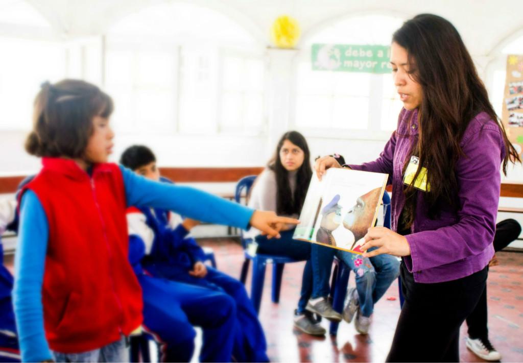 Voluntaria a cargo del LIVA: Alexandra Becerra le muestra las imágenes del cuento a los niños(as).