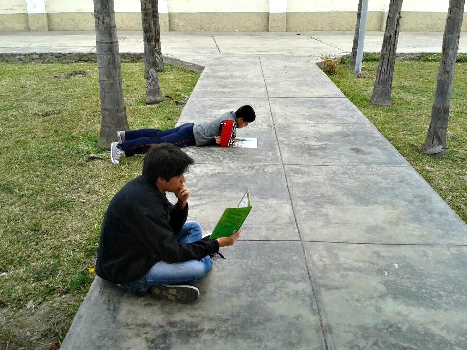 Genaro – voluntario del proyecto-  lee junto a uno de los niños de lectura divertida, en las afueras de la pérgola.