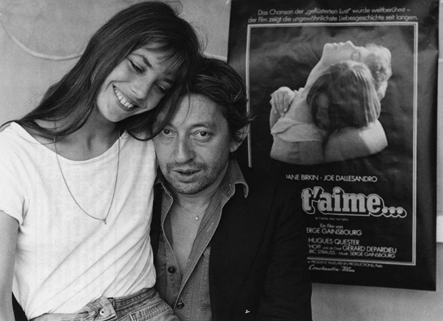 """Jane y Serge con un cartel de la película """"Je t'aime..."""" de 1976."""